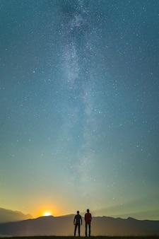 二人の男は天の川の背景に立っています。夜の時間
