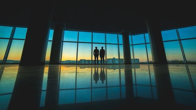 Двое мужчин стоят на фоне панорамного окна.