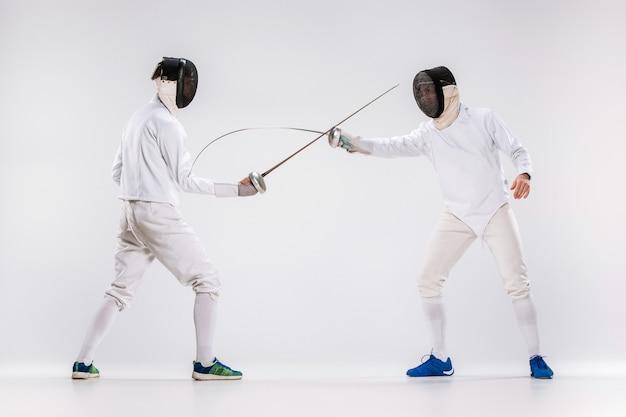 灰色に対して剣で練習フェンシングスーツを着ている2人の男性