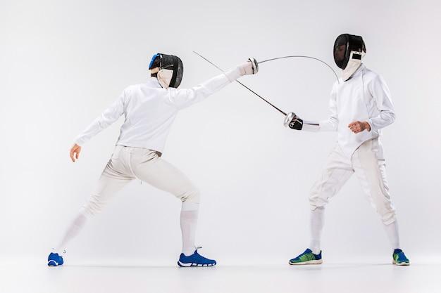 Двое мужчин в фехтовальном костюме тренируются с мечом на сером