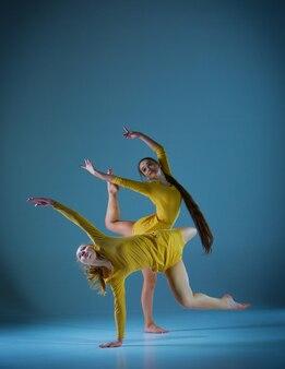 Две современные балерины танцуют на сером фоне