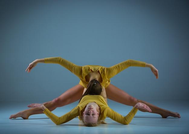 Две современные балерины позируют на сером фоне