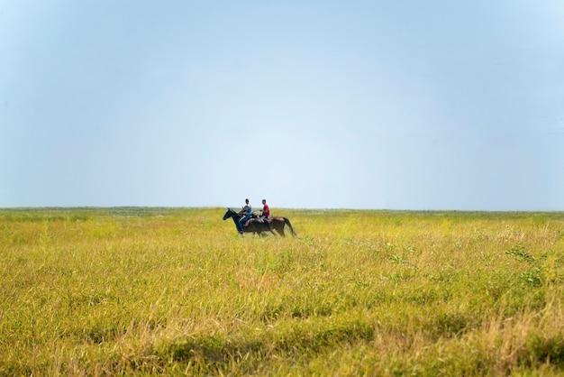 야생의 자연 속에서 들판에서 두 마리의 말을 타고 있는 두 사람