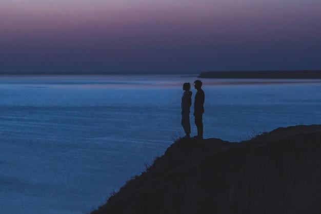 海の近くの山の端に立っている二人