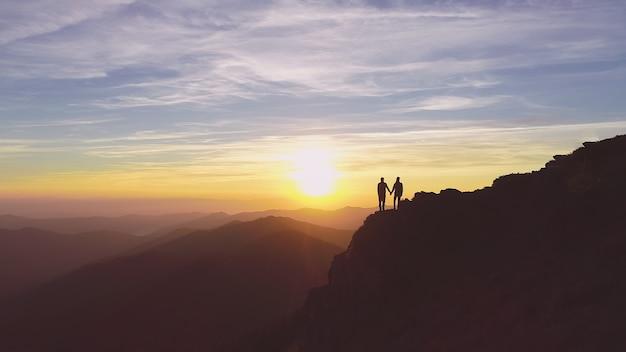 美しい夕日を背景に山に立っている二人