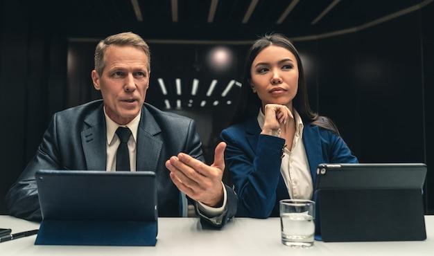 テーブルに座っている2人の笑顔のビジネスマン