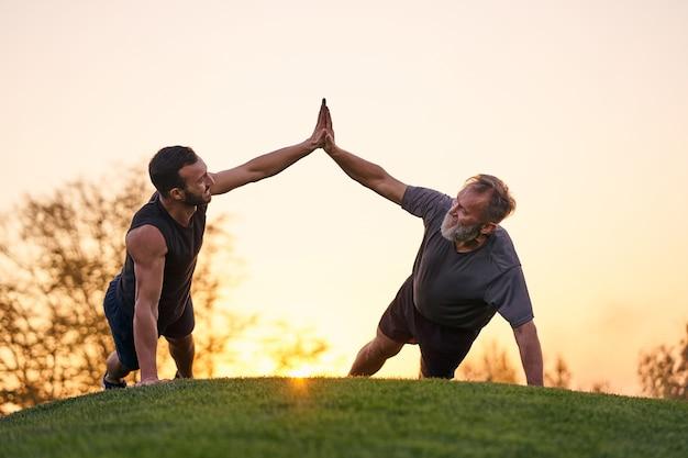 Два спортсмена вместе отжимаются на фоне заката