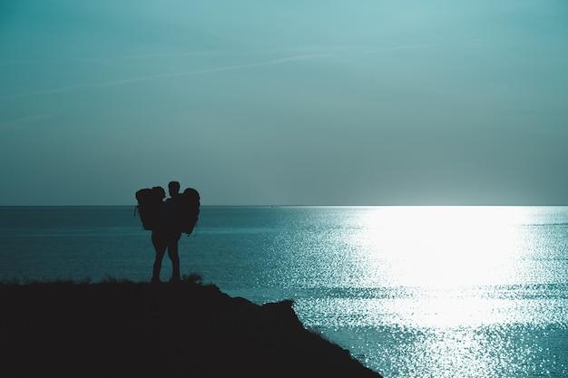 Двое путешественников с рюкзаками стоят на вершине горы у моря
