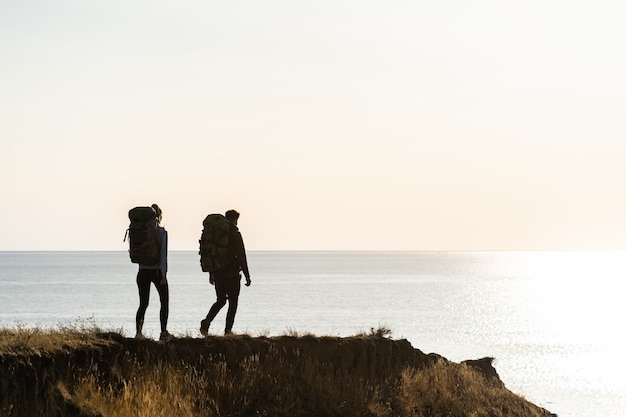 Двое путешественников с рюкзаками гуляют на вершине горы у моря