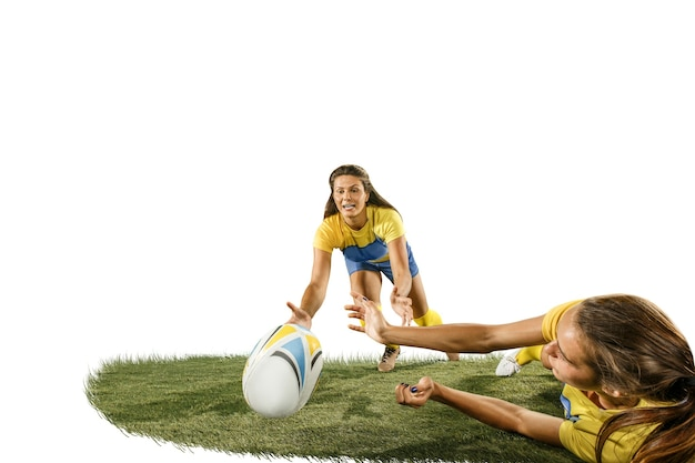 녹색 잔디와 흰색 스튜디오 backround에 고립 된 두 젊은 여성 럭비 선수. 인간의 감정. 백인 맞는 여자. 스포츠 경쟁, 모션, 운동, 싸움, 대결, 공격