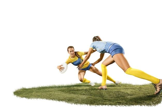 緑の草と白いスタジオのバックラウンドで隔離された2人の若い女性のラグビー選手。人間の感情。白人に合う女の子。スポーツ競技、運動、運動、戦い、対立、攻撃