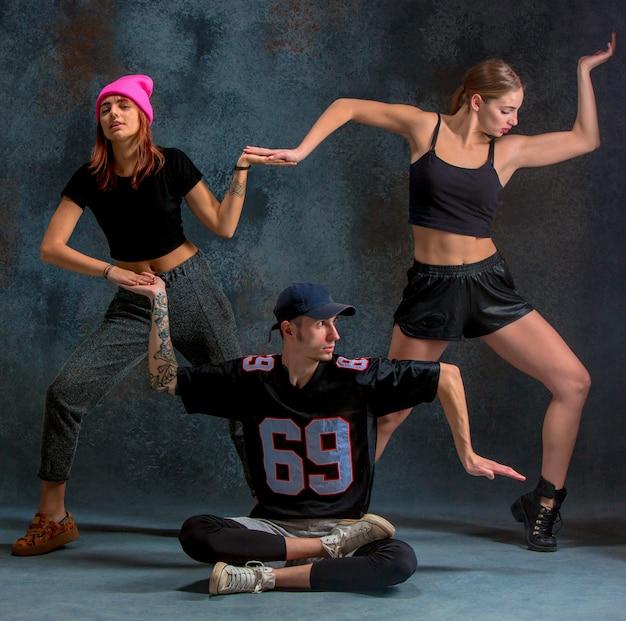 Две молодые девушки и мальчик танцуют хип-хоп в голубом