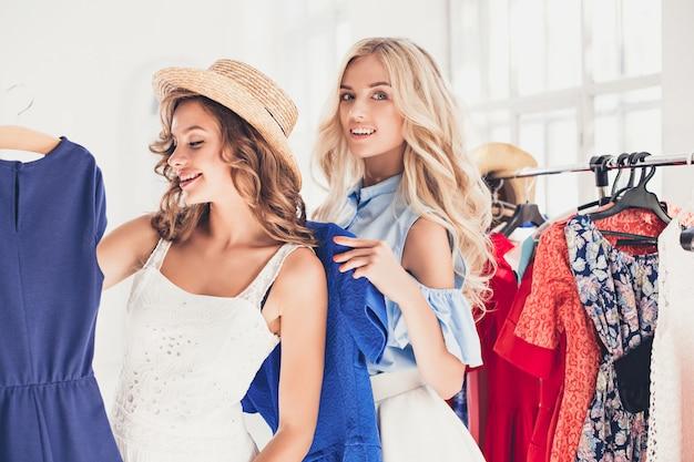 Две молодые красивые девушки смотрят на платья и примеряют их, выбирая в магазине