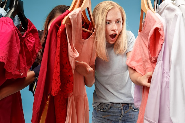 ドレスを見て、店で選ぶときにそれを試着する2人の若いきれいな女性