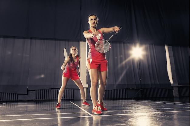 Две молодые женщины играют в бадминтон над тренажерным залом. концептуальная игра в паре