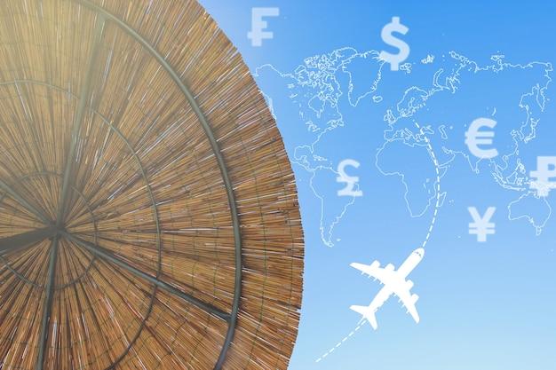 さまざまな国の通貨アイコン、世界地図のシルエット、飛行機、朝日が描かれたバンブーブラーの背景の傘。コンセプトトラベル。