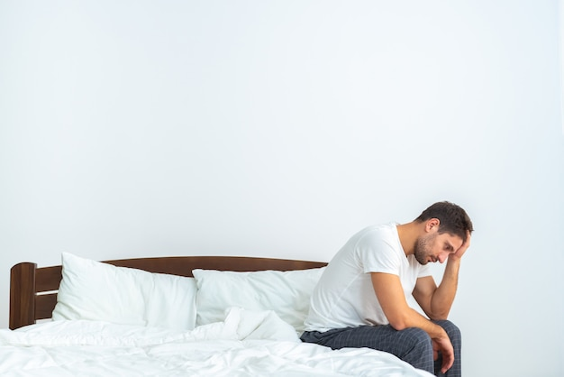 白い背景の上のベッドに座っている不幸な男