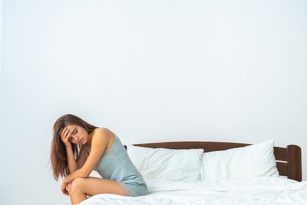 白い背景の上のベッドに座っている不幸な女性