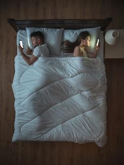 Расстроенная пара с телефоном лежит на кровати. вид сверху
