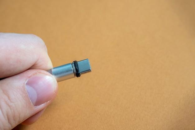 Usb 유형 c 케이블은 갈색 배경에 손에 자석 부착물로 접을 수 있습니다. 복사 공간
