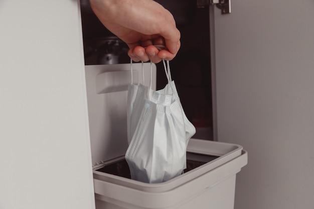 사용한 안면 마스크는 쓰레기통에 버려집니다. 일회용 수술 용 안면 마스크 폐기. 코로나 바이러스 건강 격리. 마스크 재활용 문제