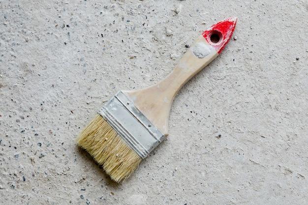 Использованная большая плоская кисть лежит на бетонной поверхности.