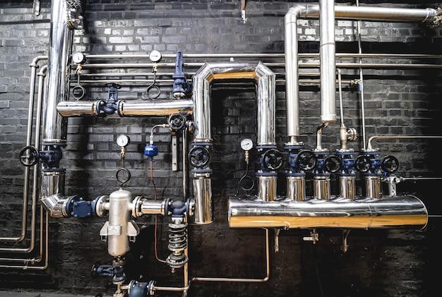 현대식 양조장 벽의 밸브와 파이프