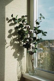 窓の上の花瓶に乾燥した植物植物と綿の茎が付いている花瓶
