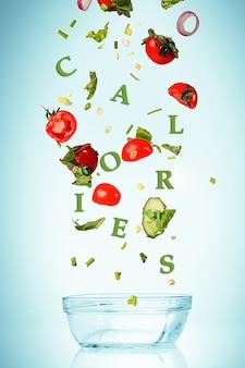 青の空のガラスのボウルに落ちるサラダ用野菜。ダイエットと健康的なライフスタイルの概念
