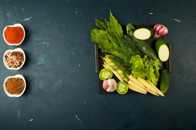 돌 상자에 야채는 어둡습니다. 어린 마늘 양파 zucchini 밝은 향신료는 어두운 질감에 손잡이가 달린 나무 쟁반에 놓여 있습니다.
