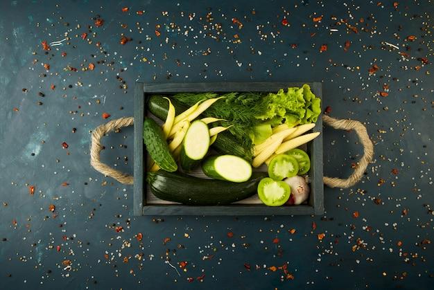 돌 상자에 야채는 어둡습니다. 어린 양파 양파 마늘 녹색 콩 노란색 옥수수 주키니 밝은 향신료는 어두운 질감의 로프 핸들이 달린 나무 상자에 들어 있습니다.