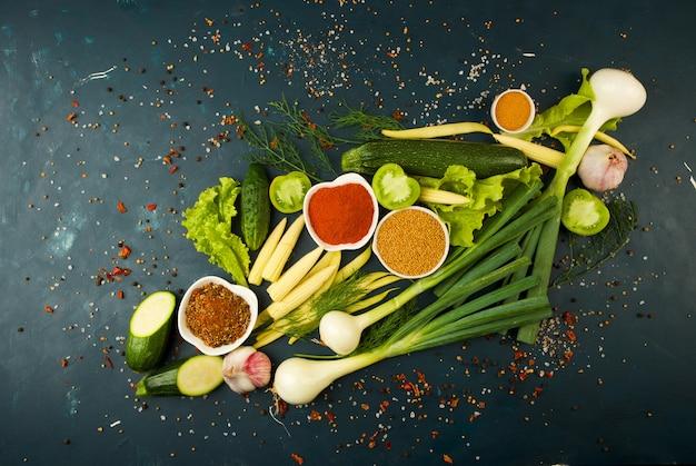 ストーン・ア・ダークの野菜。ヤングハーブオニオンズニンニクグリーンビーンズイエローコーンズッキーニスパイスは、暗いテクスチャーで鮮やかです。
