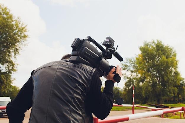 ビデオ撮影者はレポートに取り組んでいます。