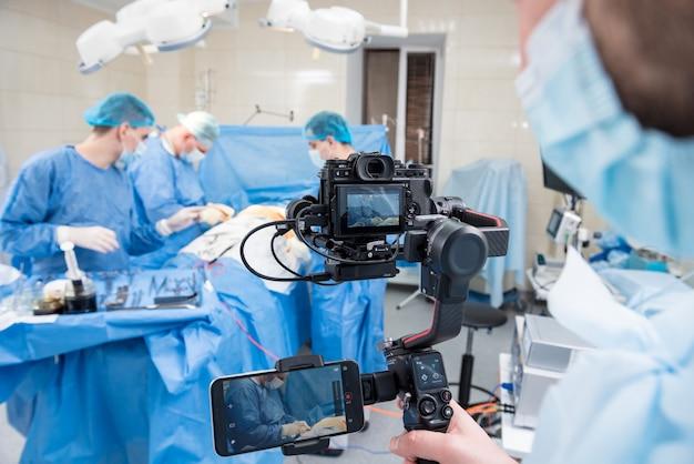 ビデオグラファーは、手術室で手術器具を使って外科医と助手を撮影します