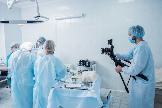 ビデオグラファーは外科医と助手を撮影します