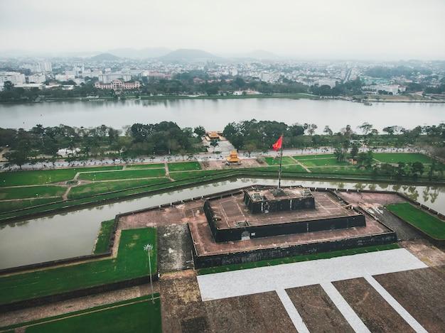 베트남 허우에 있는 황궁 앞 무대 위에서 흔드는 베트남 국기. 공중 샷입니다.