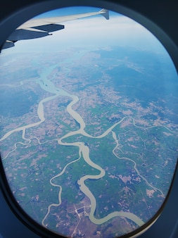 Вид из иллюминатора самолета на землю. пейзажный вид с неба.
