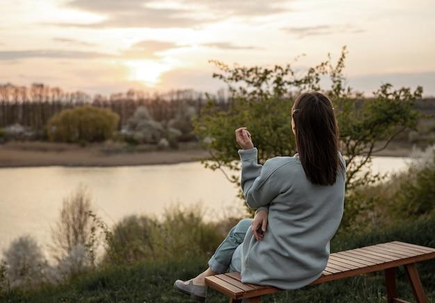 少女の後ろからの眺めは、ベンチに座って夕日を眺めています。