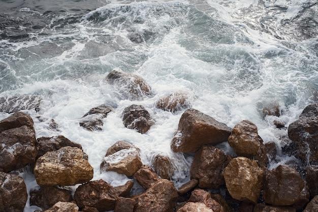 날카로운 절벽에 부서지는 하얀 거품과 함께 바다 파도의 꼭대기에서 보기 프리미엄 사진