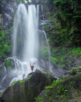 Вид на водопад, под которым стоит человек, действительно красив в индонезии.