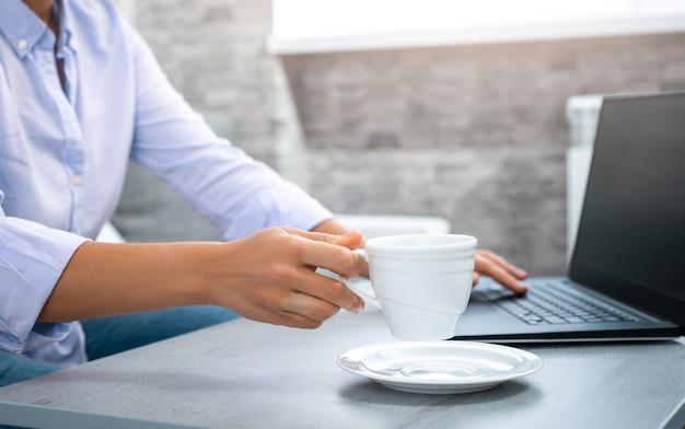 ノートパソコンを背景にカップを上げている女性の手のビュー。ラップトップ。自宅からのリモートワーク。
