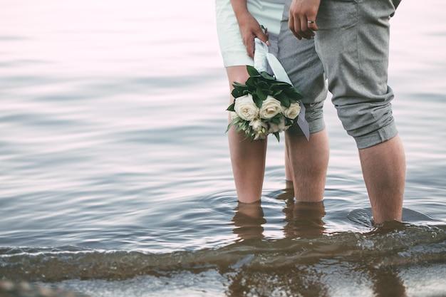 Вид на ноги молодоженов, стоящих на пляже. вид на свадебный букет из белых роз и хлопка