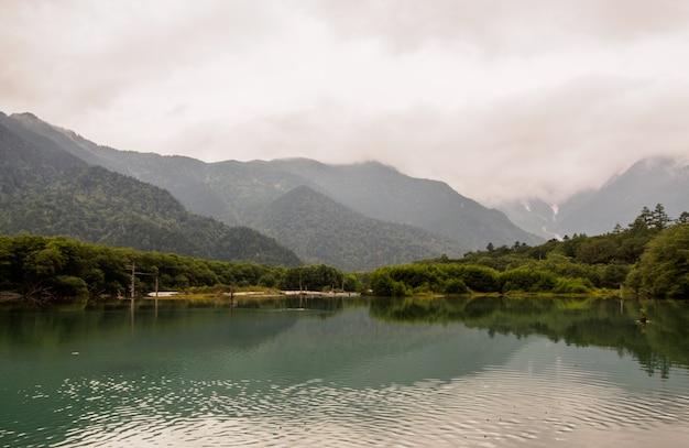 上高地日本の雲を背景に山の森を流れる小川の景色