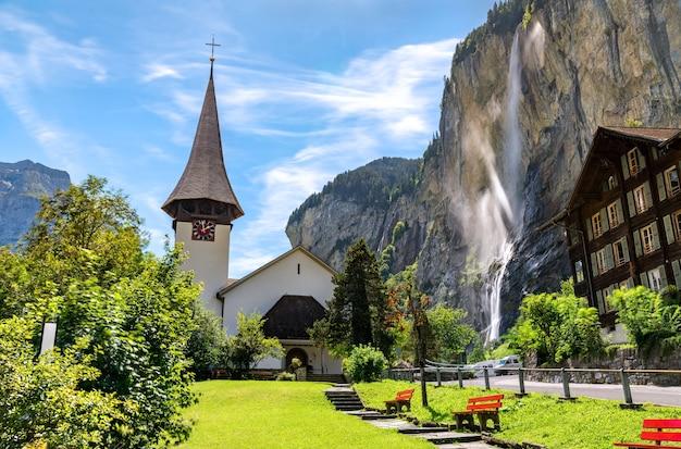 Деревенская церковь и водопад штауббах в лаутербруннене в швейцарских альпах