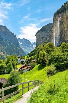 Деревенская церковь и водопад штауббах в лаутербруннене в швейцарии