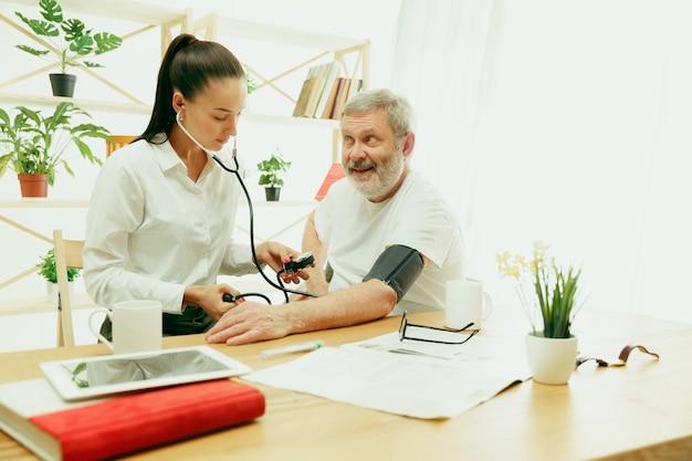 방문 간호사 또는 노인을 돌보는 건강 방문자. 집에서 라이프 스타일 초상화. 의학, 건강 관리 및 예방. 방문하는 동안 환자의 혈압을 확인하거나 측정하는 소녀.