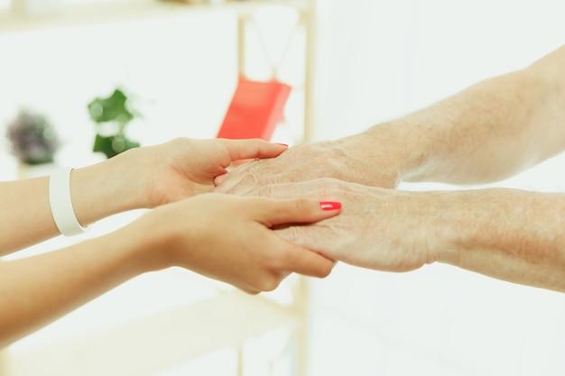 年配の男性の世話をする訪問看護師