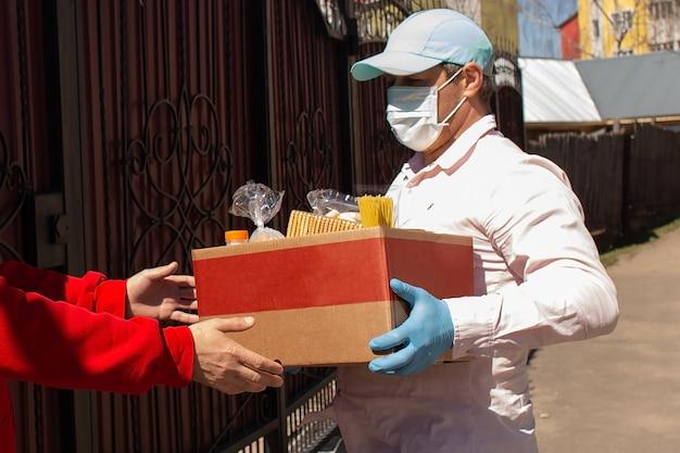 Волонтер вручает нуждающимся коробку с едой.