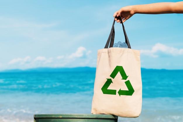 Волонтер держит пластиковый пакет в мусорном ведре