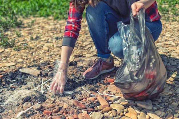 Волонтера удаляют в лес после сезона пикников и барбекю. женщина собирает пластиковые вилки на старом костре. день земли и концепция улучшения окружающей среды